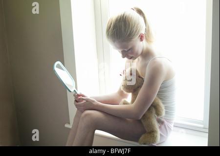girl w teddy bear near window looking at mirror - Stock Photo