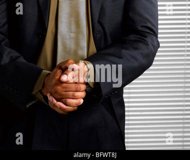 Business man wringing hands together - Stock Photo