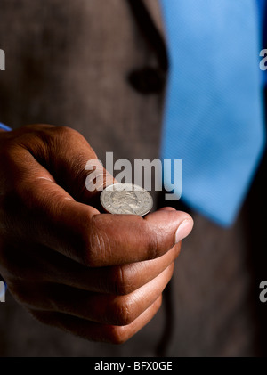 Business man ready to flip sterling coin - Stock Photo