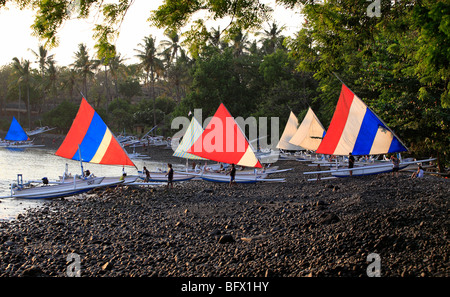 Jukungs, or Balinese fishing boats, pulled up on the beach, early morning. Tulamben, Bali, Indonesia - Stock Photo