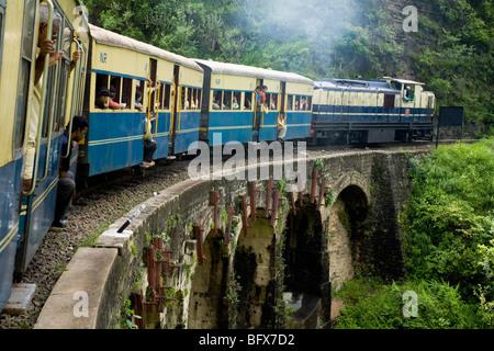 Train and carriages cross bridge number 493 on the Kalka-Shimla Railway. Shimla, India. - Stock Photo