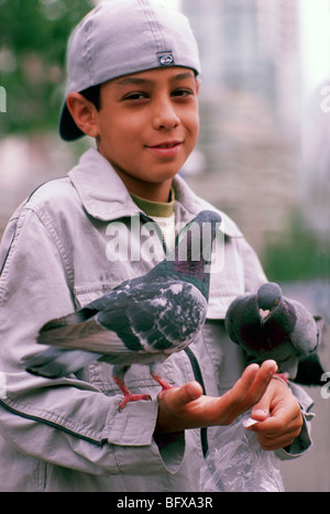 Young Boy feeding Birds, Child holding Pigeons, Granville Island, Vancouver, BC, British Columbia, Canada - Stock Photo