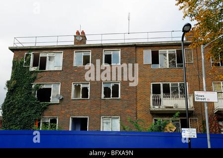 Derelict flats behind hoardings Hackney London England UK - Stock Photo