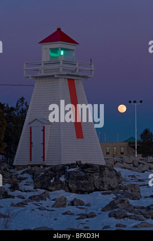 Moonrise over lighthouse and Ferry terminal buildings at South Bay, South Bay, Manitoulin Island, Ontario, Canada - Stock Photo