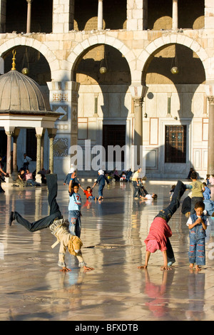 Muslim girls doing flips in the Umayyad Mosque in Damascus Syria - Stock Photo