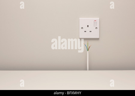 Bare wires by an electrical wall socket - Stock Photo