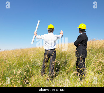 contractors with blueprints in field - Stock Photo