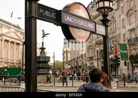 tourists near Piccadilly Underground Station with view of Eros statue behind - Stock Photo