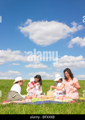 young people on picnic blanket - Stock Photo