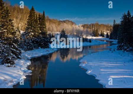 Open water of junction Creek with shoreline spruces and birches, Greater Sudbury, Ontario, Canada - Stock Photo