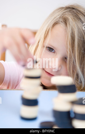 Young girl making tower out of dominoes - Stock Photo