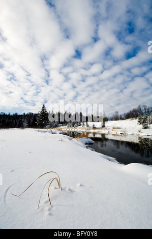 Open water of Junction Creek with fresh snow and afternoon clouds, Greater Sudbury, Ontario, Canada - Stock Photo