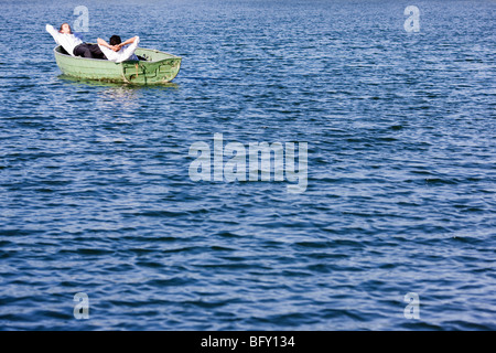 two businessmen relaxing in rowboat - Stock Photo