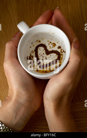 Woman looking at heart in tea leaves - Stock Photo