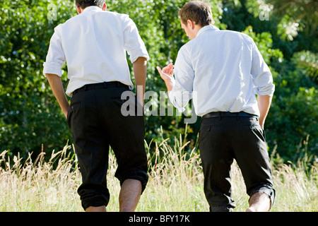 two businessmen talking in field - Stock Photo