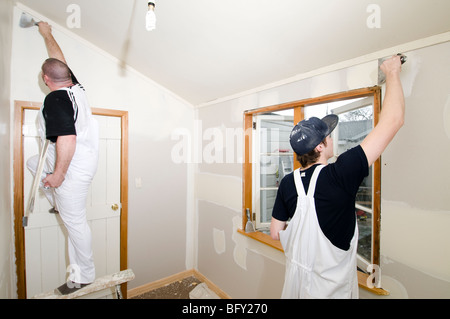 Man and apprentice plastering room - Stock Photo