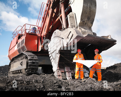 Coal Miners With Plans And Digger - Stock Photo