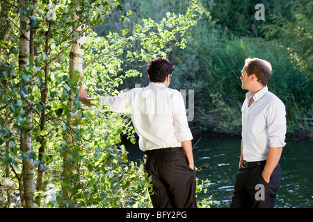 two businessmen talking on lakefront - Stock Photo