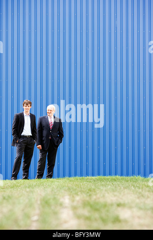 two businessmen in front of storage - Stock Photo