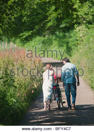 Man and woman walking up country lane - Stock Photo