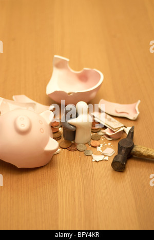 small figures and smashed piggy bank - Stock Photo