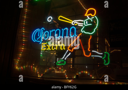 An illuminated neon sign advertising Corona Extra Mexican beer in the window of a bar in Williamsburg, Brooklyn - Stock Photo