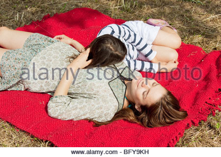 Mother and daughter lie on red blanket - Stock Photo