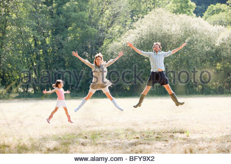 Family jumping in country field - Stock Photo