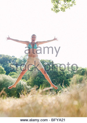 Woman in bikini jumping in country field - Stock Photo