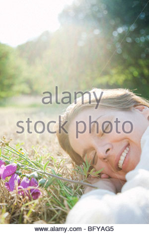 Woman lying in grass with flowers - Stock Photo