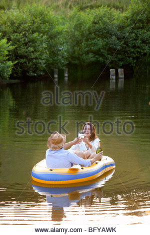 Couple in dinghy on a country lake - Stock Photo