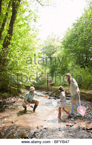 Family playing in country stream - Stock Photo