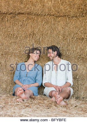 Man and woman sitting against hay bale - Stock Photo