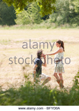 man on knees kissing womans hand - Stock Photo