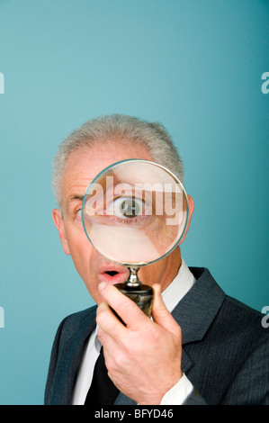 Businessman holding magnifying glass over eye - Stock Photo