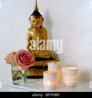 Golden Buddha statue, pink roses and candles on a shelf - Stock Photo