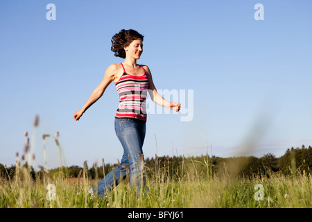 Woman Running Through Meadow - Stock Photo