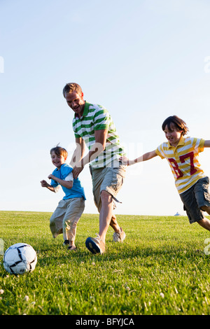 Father and Two Sons Playing Soccer - Stock Photo