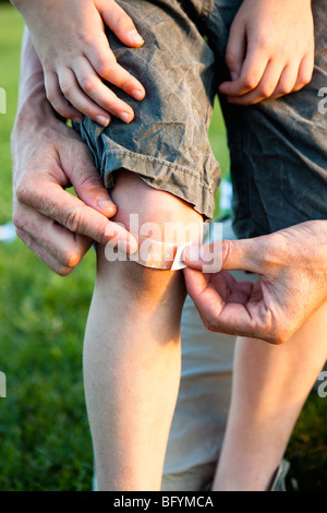 Father Applying Bandage to Knee close-up - Stock Photo