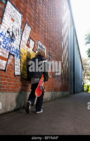 rear view of young boy walking along wall with skatebord - Stock Photo
