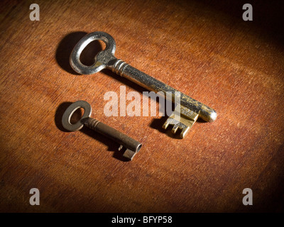 Two obsoletes keys over a wooden table. - Stock Photo