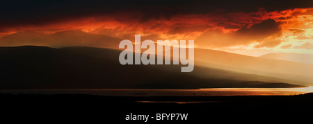 Stunning fiery red sunset over Loch Shin mountain area, Sutherland, Northern Scotland, UK taken from A838 in panoramic - Stock Photo