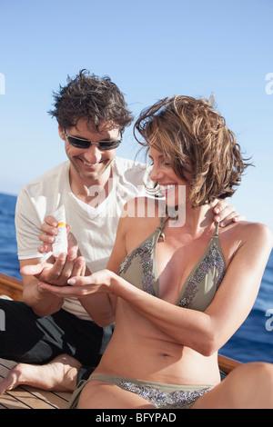 couple laughing applying suntan lotion - Stock Photo