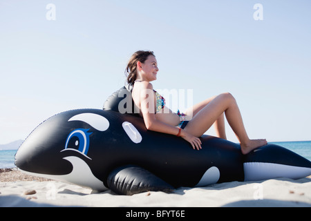 young girl sitting on toy whale - Stock Photo