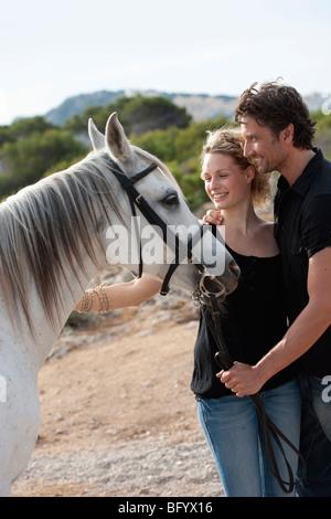 couple smiling holding horse - Stock Photo