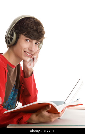 Teenage boy sitting behind desk reading book and listening music isolated on white background - Stock Photo