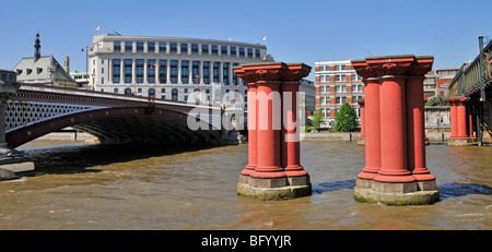 Remaining columns of disused Blackfriars railway bridge over River Thames with Blackfriars road bridge & Unilever - Stock Photo
