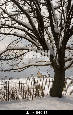 Cemetery view in snow on a gloomy winter day. - Stock Photo