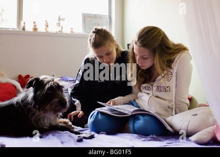 Teens in bedroom doing homework - Stock Photo