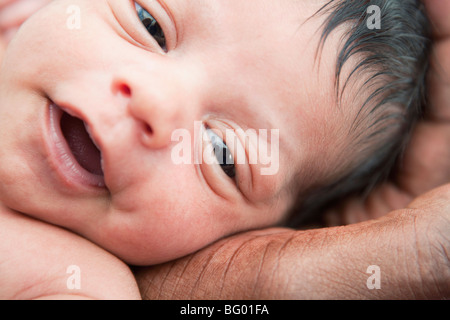 Baby's head in fathers hand - Stock Photo